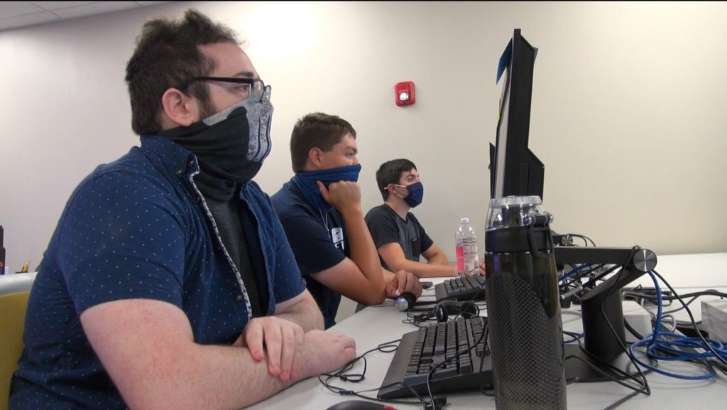 Three students, wearing face masks are sitting at their computers in a classroom.
